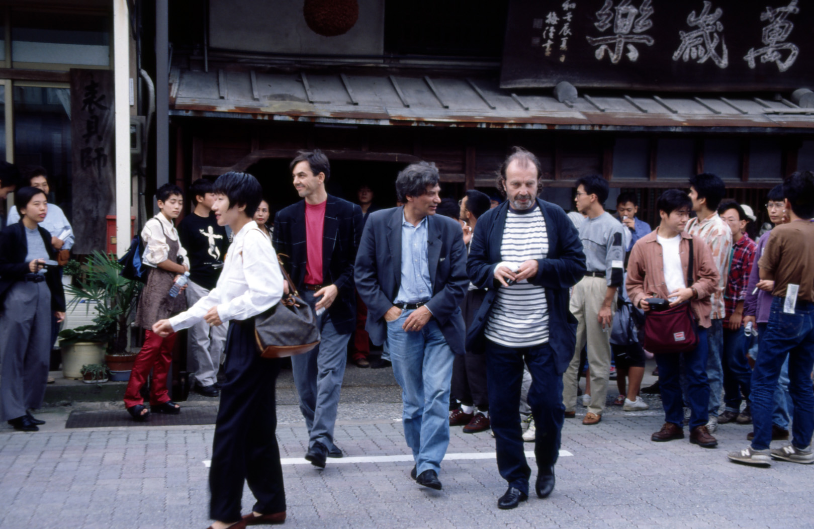 "Jan Hoet (center), Franz West (right), and West's assistant during the walking talk for the exhibition ""Jan Hoet in Tsurugi,"" in front of the main store of Manzairaku, sake brewery, Hakusan, Ishikawa, September 25, 1994."