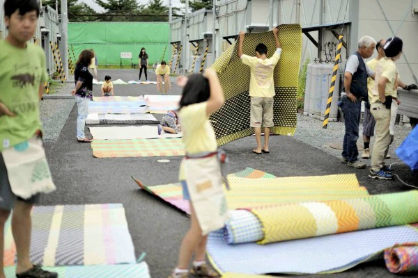 [Image 3. Children spread out hand-made mats to prepare the market. The 11th My Town Market (9th August 2014) at Ogawa Park Temporary Housing, Shinchi-cho, Fukushima Prefecture. Photo by Yuji ITŌ]