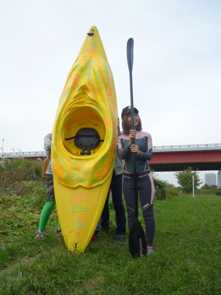"[Figure 1: Rokudenashiko stands by her ""man-boat"" kayak, whose top attachment was modeled on her vulva, on the banks of the Tamagawa River. (Credit: Taishiro Sakurai)]"